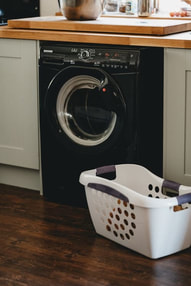 Photo of a black washing machine with a laundry basket in front